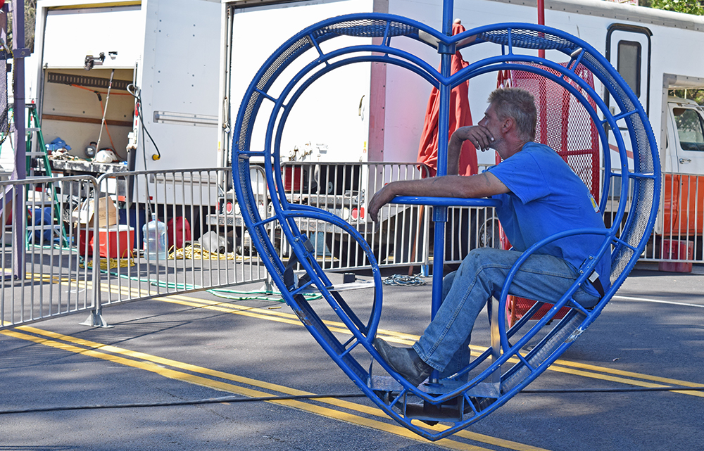 """BLUE: An operator of the ride dubbed """"The Twister"""" waited patiently for festival goers to ride. Although COFECA featured small several carnival rides that required ticket purchases to participate, few of them were operating on Saturday morning."""